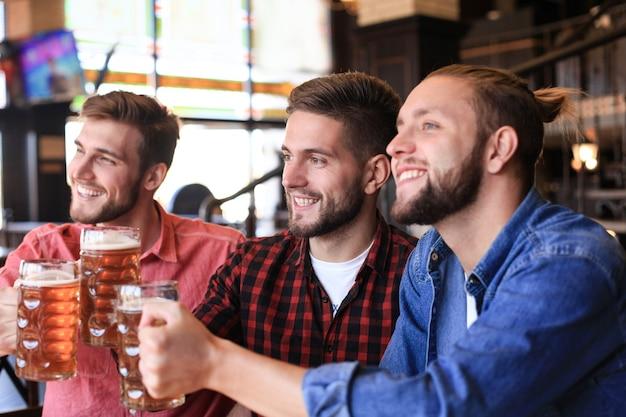 パブのバーカウンターでドラフトビールを楽しんで飲んでいる陽気な古くからの友人。
