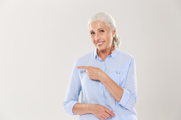 Cheerful old lady in blue shirt, pointing with finger on the empty copyspace