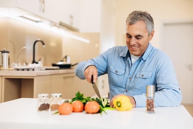 Веселый старик режет ножом овощи на кухне с белой мебелью