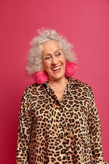 Жизнерадостная старушка наслаждается жизнью, широко улыбается, у нее идеальные белые зубы, смотрит в сторону с радостным выражением лица, носит пушистые серьги и платье с леопардовым принтом, вспоминает молодость, вспоминает что-то очень приятное