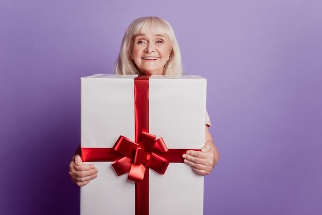 Веселая старуха держит большую подарочную коробку, изолированную на фиолетовом фоне