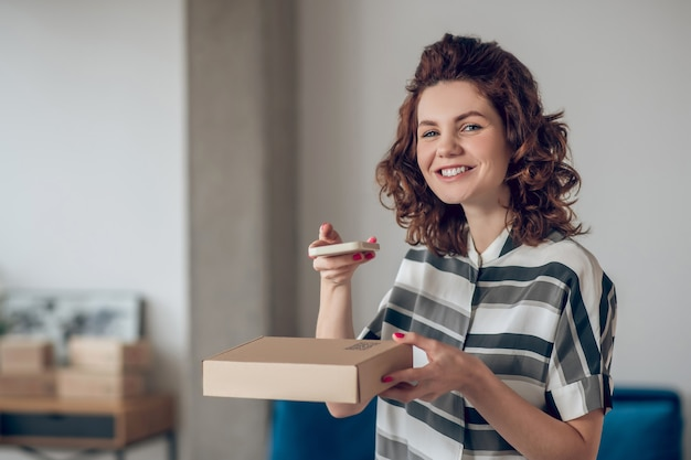 Cheerful online store worker posing for the camera in the workplace