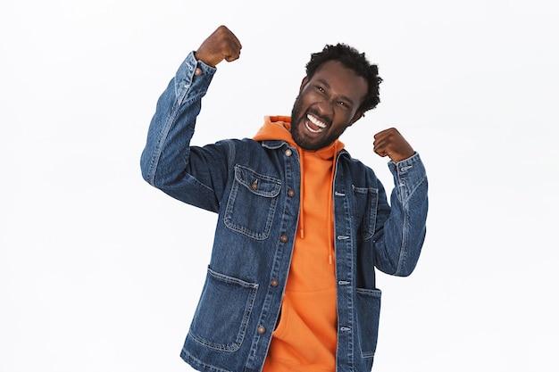 陽気で楽観的で安心したハンサムなアフリカ系アメリカ人の男が喜びと喜びで勝利し、成功を収める