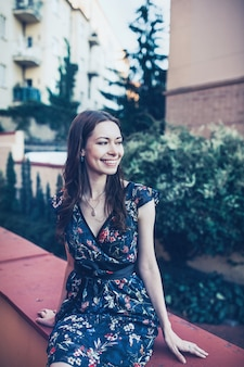 Веселая оптимистичная брюнетка в цветочном платье сидит на открытом воздухе