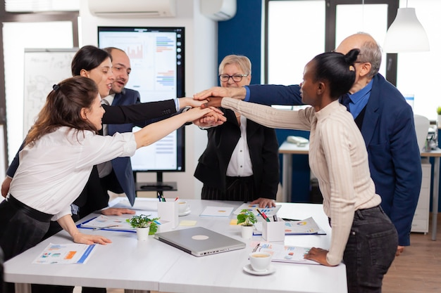 Cheerful overjoyed business people in conference room celerating diverse colleagues with new opportunity enjoing victory meeting in broadroom office