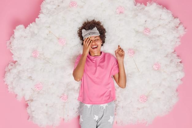 陽気な大喜びの縮れ毛のアフリカ系アメリカ人女性は楽しまれて幸せに笑う