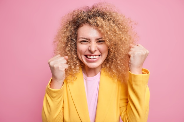 Cheerful overjoyed curly haired businesswoman clenches fists like champion celebrates victory hears excellent news dressed in yellow jacket isolated over pink wall. triumphing corporate woman