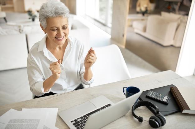 Allegro felicissimo elegante agente immobiliare femmina matura che stringe i pugni, esprimendo eccitazione dopo aver fatto un buon affare online, sorridendo ampiamente, seduto davanti al laptop aperto