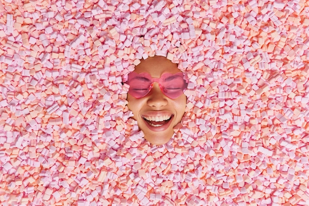 Cheerful overjoyed ethnic woman smiles broadly shows white teeth wears trendy sunglasses has fun poses among appetizing soft marshmallow eats delicious dessert