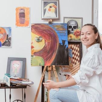Веселый художник сидит возле картины в студии