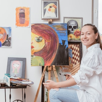Cheerful painter sitting near picture in studio