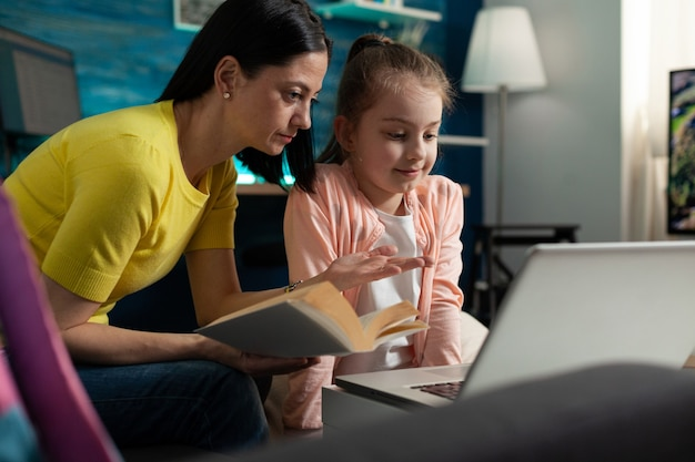 Cheerful parent holding literature book in hands helping daughter with school homework