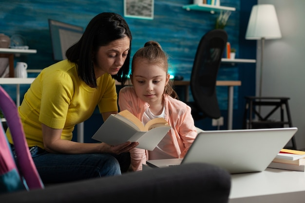 Cheerful parent sitting beside daughter holding school book reading together