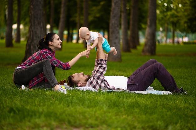 쾌활한 부모와 작은 아기가 여름 공원에서 잔디에서 재생