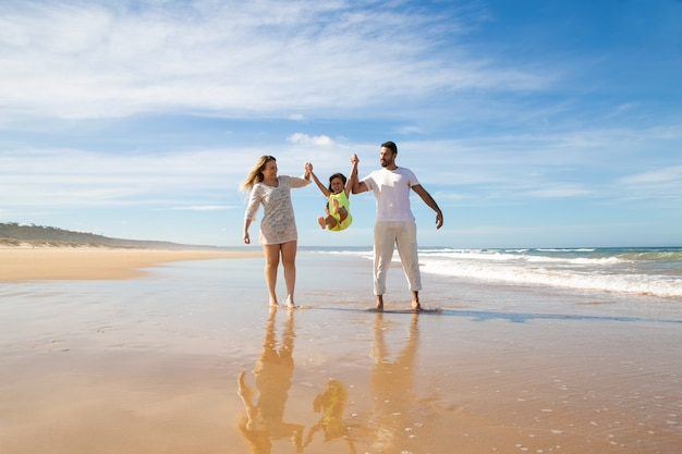 陽気な両親とビーチでのウォーキングやアクティビティを楽しんでいる小さな女の子、両親の手を握って、ジャンプして足を上げて子供