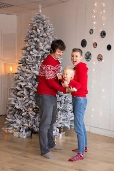 陽気な両親と家でクリスマスを待っている彼らのかわいい息子の男の子。家で家族のクリスマス。
