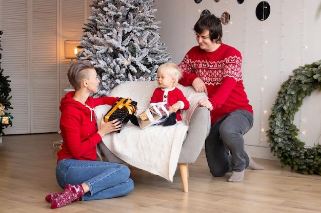 陽気な両親とその幼い息子が贈り物を交換します。メリークリスマスとハッピーホリデー