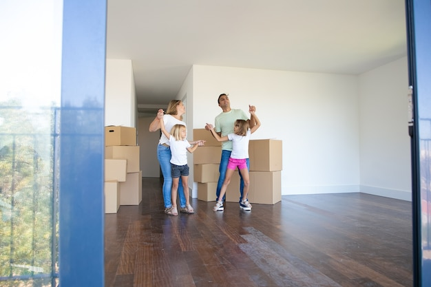 Cheerful parents and daughters dancing and having fun near heaps of boxes while moving into new flat