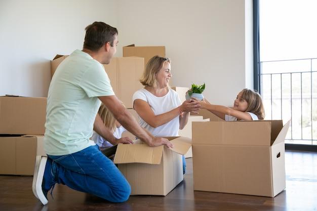 Genitori e bambini allegri che disimballano le cose nel nuovo appartamento, seduti sul pavimento e prendono la pianta d'appartamento dalla scatola aperta