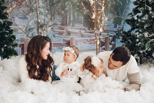 Cheerful parents lying in artificial snow with their sweet daughters