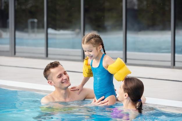 Веселые родители играют со своей очаровательной маленькой дочкой в бассейне перед камерой, проводя выходные вместе в спа-центре