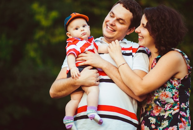 Cheerful parents smile to little son on their arms