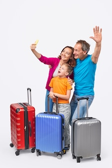 Cheerful parents and son smiling and posing for selfie while standing behind suitcases before trip against white background