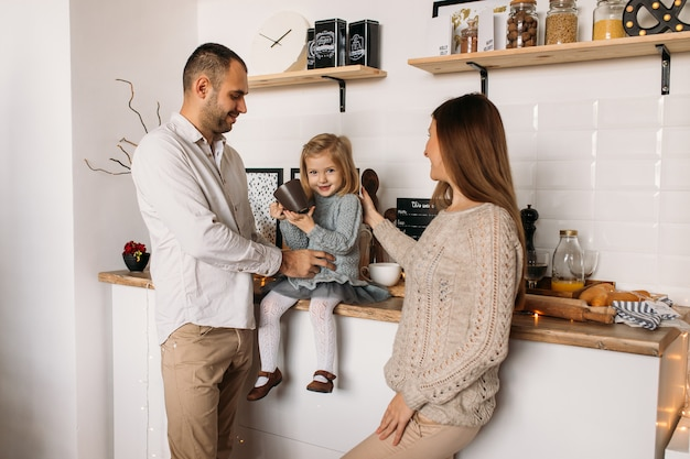 Cheerful parents and their cute daughter girl in kitchen at home.