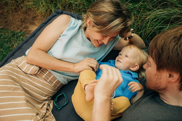 Cheerful parents tickling child lying outdoors