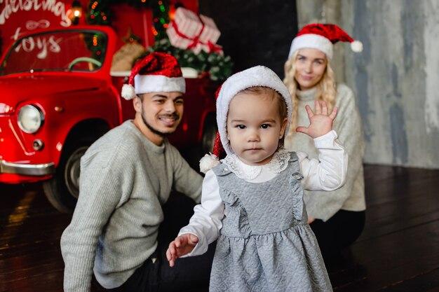 Веселые родители с дочерью на шляпе санты дома с рождественским фоном.