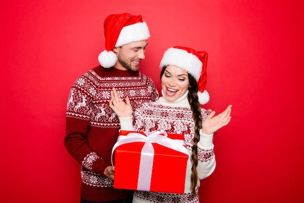Веселый партнер в вязаной одежде держит упакованную коробку с дамой Premium Фотографии