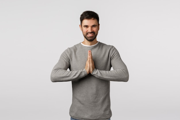 Cheerful and peaceful adult male yoga instructor teaching how release stress, bowing namaste gesture, hold hands pressed together over chest, praying, smiling delighted, asking help or thanking