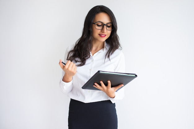 Cheerful pensive business lady examining papers