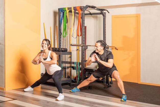 ジムで内転筋ストレッチ運動をしている元気な人、カメラを見ている女性。ジムでの運動の概念。