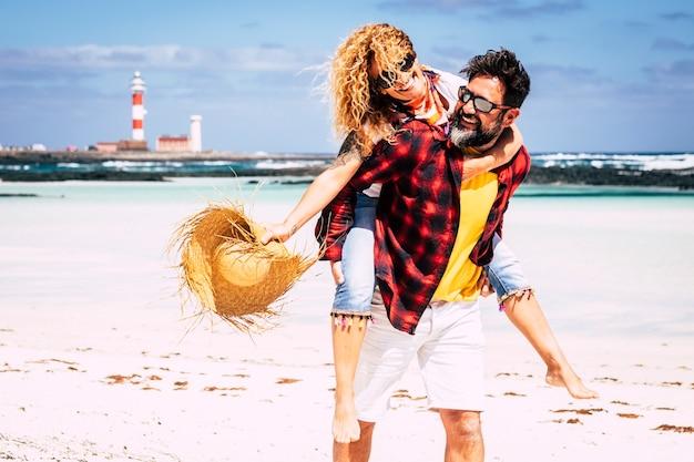夏休みの晴れた日にビーチで楽しんで笑っている女性を運ぶ男性と恋に一緒に遊ぶ陽気な人々幸せな喜びに満ちたカップル