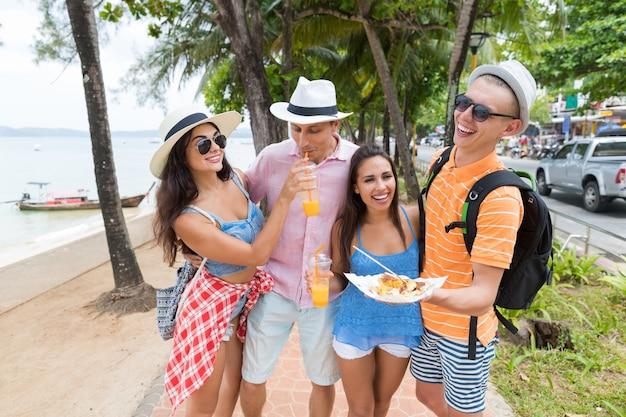 Cheerful people on seaside group of friends holding asian street food walk