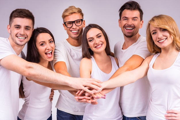 Cheerful people stand together and hold hands.
