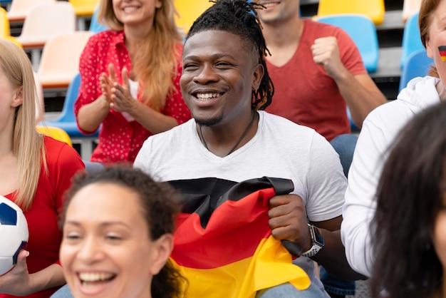 サッカーの試合を見ている陽気な人々