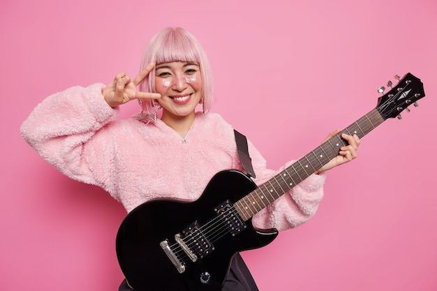 Cheerful pink haired female guitarist poses with electric guitar plays music dressed in fur coat makes disco sign feels happy poses at studio. professional singer keen on rock shows victory gesture