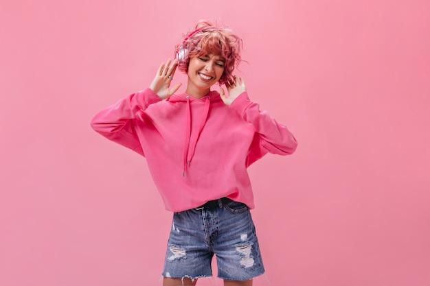 Веселая розоволосая женщина в джинсовых шортах и огромном худи слушает музыку в наушниках и танцует на изолированной стене