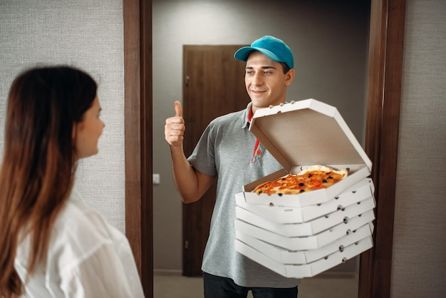 Cheerful pizza delivery boy shows thumbs up symbol to female customer