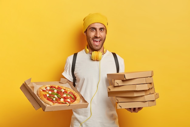Cheerful pizza delivery man stands with carton boxes, waits for client, wears yellow hat and white t shirt, listens music during transporting fast food