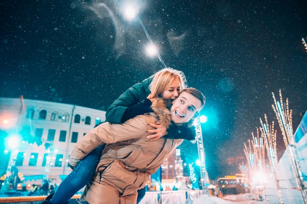 Cheerful and playful couple in warm winter outfits are fooling around