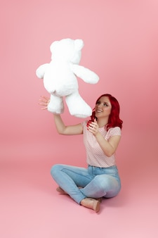 A cheerful, playful woman with red hair and wearing jeans throws up a large white teddy bear
