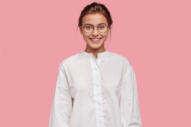 Allegra donna dall'aspetto piacevole in occhiali, ha un'espressione felice, vestita in camicia bianca