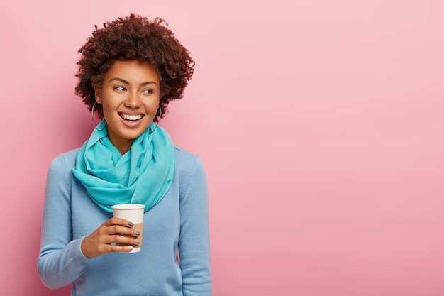 Cheerful pleasant looking woman with afro hair drinks takeaway coffee, enjoys rest after hard working day, has pleasant talk looks aside with toothy smile dressed in blue clothes isolated on pink wall