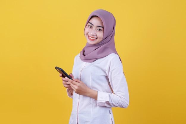 Веселая довольная азиатская женщина общается по мобильному телефону, активно жестикулирует, делает покупки в интернете, носит хиджаб