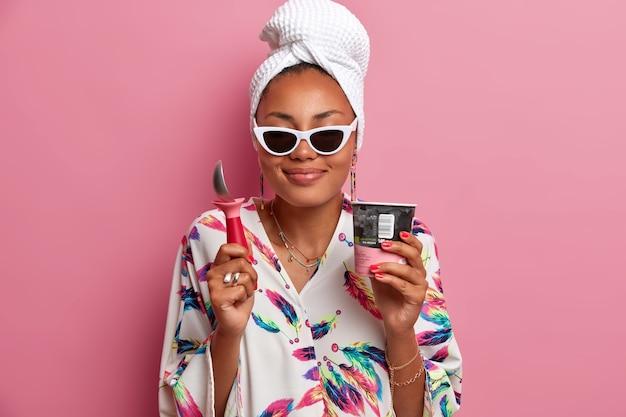 陽気で喜んでいる暗い肌の女性は、ストロベリーアイスクリームの心地よい味を楽しんで、食べるためのスプーンを持って、ピンクの壁に隔離されて、家で夏休みを過ごします。冷菓