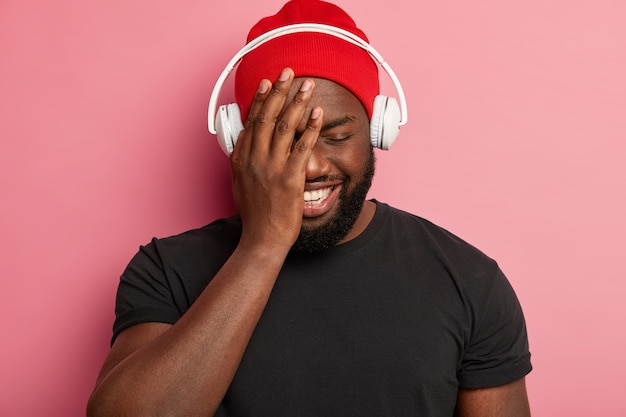 Cheerful pleased guy in red hat, closes eyes, smiles broadly, chooses song for relaxation wears stereo headphones, isolated on pink wall, spends free time listening music.