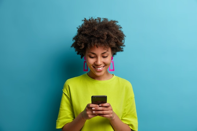 Cheerful pleased woman with curly hair holds mobile phone and texts with friends in social networks, uses special application, watches interesting video, isolated on blue wall. people and technology